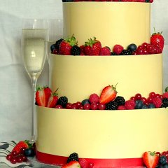A glamorous, three-tier white chocolate, lemon and berry wedding cake