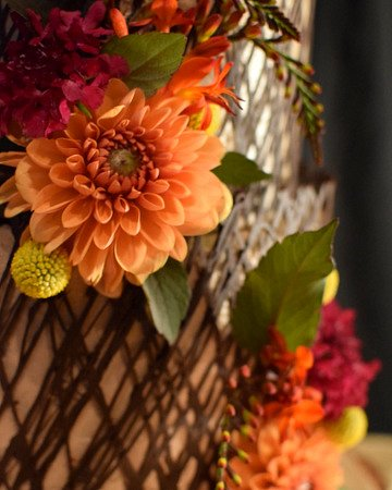 Close-up of wedding cake with dahlias and chocolate cage