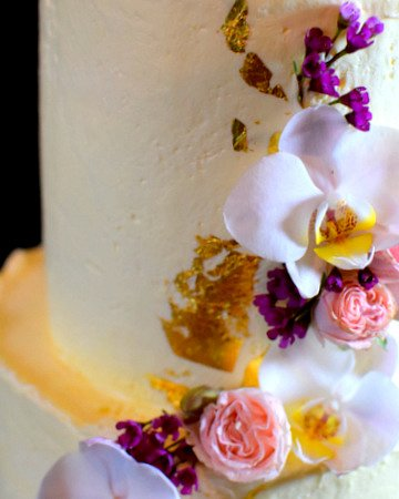Close-up of wedding cake with roses and orchids